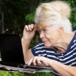 senior woman looking at screen of laptop
