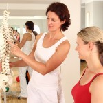 Physiotheraeutin erklärt Patientin Wirbelsäule