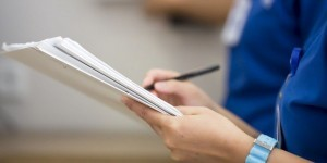 Nurse is holding a medical report, selective focus