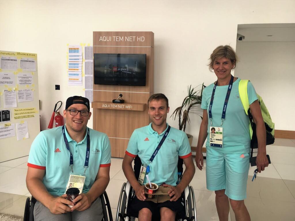 Kai Möller und Thomas Böhme (beide Spieler der Rollstuhlbasketball-Nationalmannschaft) und Bärbel Börgel in der Lobby der deutschen Wohneinheit im Paralympische Dorf.