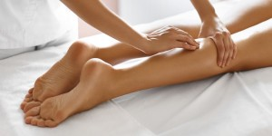 Body care. Close-up of sexy woman getting spa treatment. Leg massage therapy in spa salon. Masseur applying moisturizing oil and massaging beautiful long tanned female legs. Skin care, wellbeing, wellness concept.