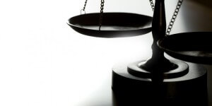 Scales of justice with back-light on wood table. Ideal for home page of law firm website. Can flop and add text as well.