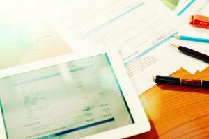 Foto von Tablet und Papier mit Rechnung