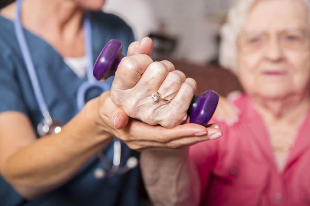 Therapeutin trainiert mit alter Frau mit Hantel