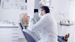 Foto von junger Frau im Zahnartstuhl mit zahnarzt