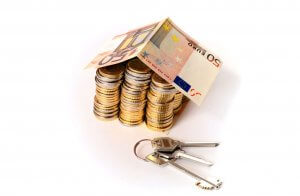 Haus aus Münzen und Geldscheinen mit Schlüsselbund