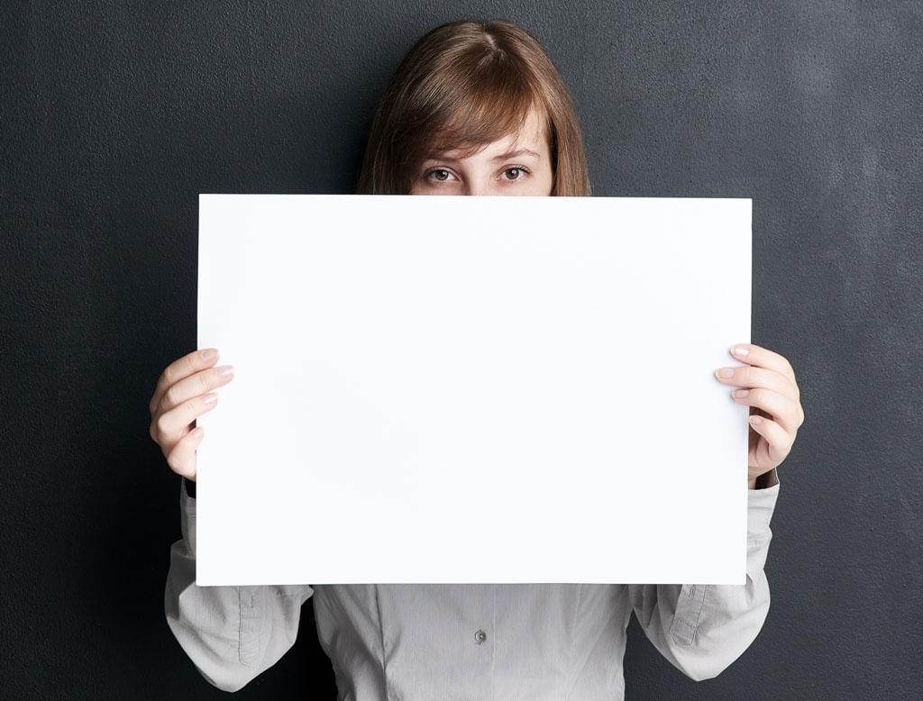 Frau hält großes Blatt Papier vor sich