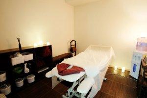 Moderner Behandlungsraum mit Liege, elektrischen Kerzen