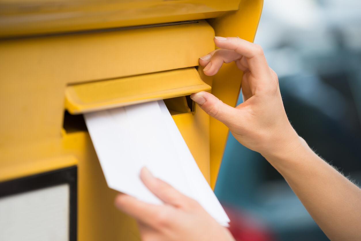 weibliche Hand wirft Brief in Postkasten ein