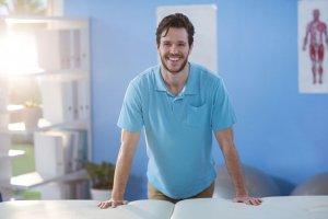 Physiotherapeut steht an Behandlungsliege