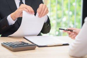 Geschäfts-Mann zerreißt Vertrag, während ihm Kugelschreiber gereicht wird